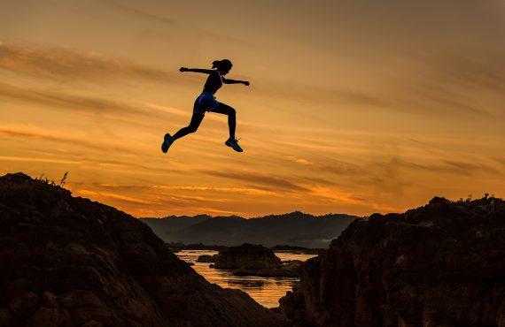 woman jump between cliffs