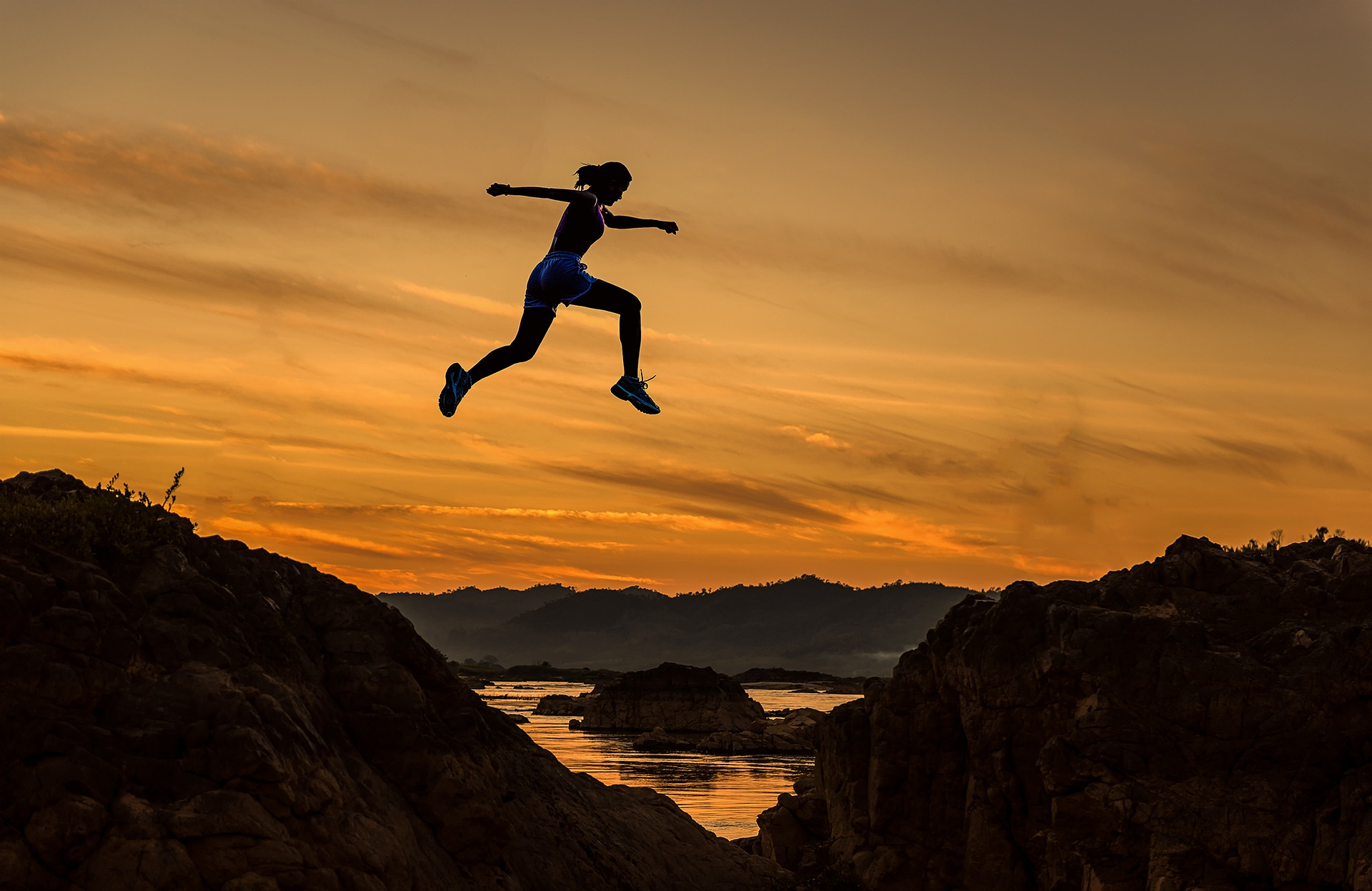 woman jump between cliffs